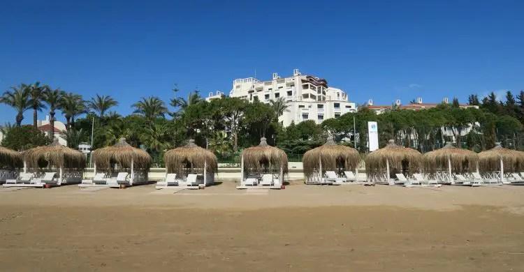 Ein weißes Hotel steht in einem Park mit Palmen. Am menschenleeren Sandstrand sind Liegestühle in kleinen Strandhütten zu sehen.