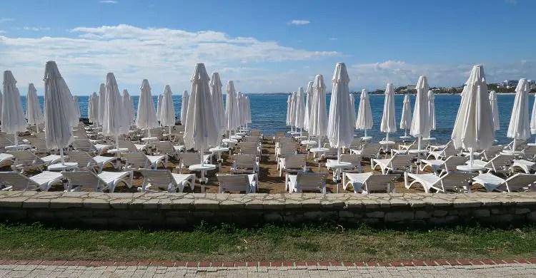 Geschlossene, weiße Sonnenschirme und weiße Sonnenliegen am Strand von Side.