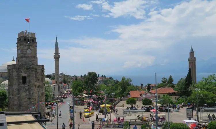 Der Uhrturm von Antalya am Tag mit dem Meer im Hintergrund.