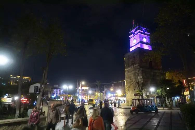"""Der Uhrturm von Antalya """"Saat Kulesi"""" während er in der Nacht violett beleuchtet ist."""