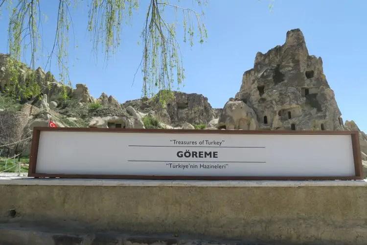 """Am weißen Eingangsschild steht """"Göreme Nationalpark"""". Dahinter sind Bäume und die Felsenkirchen im Park zu sehen."""