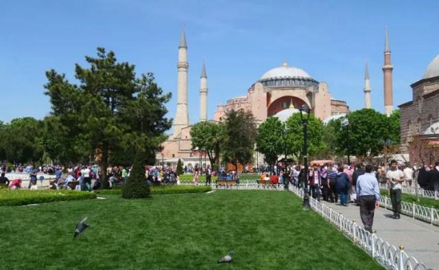 Ein Foto der Hagia Sophia in Istanbul im Mai. Das Gras ist grün, die Sonne scheint und es sind viele Reisende zu sehen.