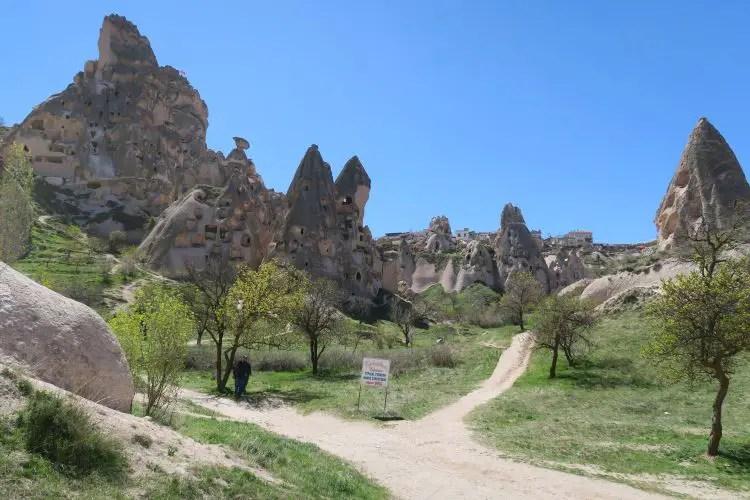 Die Festung Uchisar und das gute Wetter am Tag mit Sonnenschein, blauen Himmel und den blühenden Bäumen in Kappadokien.