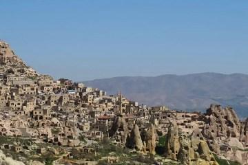 Ein Bild der Festung Uchisar in Kappadokien mit der dahinterliegenden, kargen, sandfarbenen Landschaft.