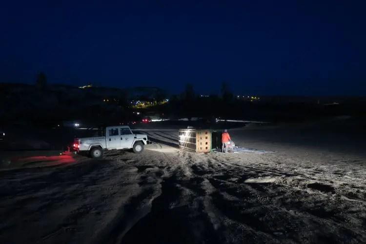 Jeep mit einem Anhänger und dem Korb eines Heißluftballons im Dunkeln.