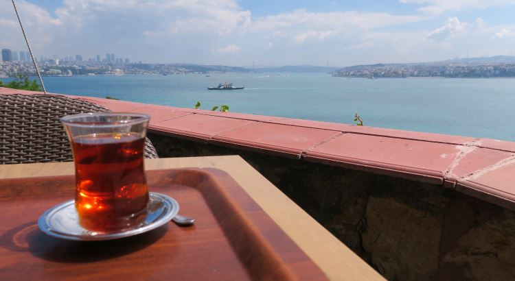 Eine Tasse Cay steht auf einem Tisch in einem Restaurant oberhalb des Bosporus mit Blick auf das Meer und die Stadt.