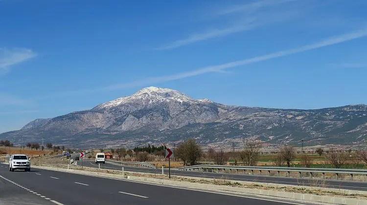 Ein Mietwagen fährt gerade am Straßenrand der Straße von Antalya nach Denizli vorbei. Im Hintergrund ist ein schneebedeckter Berg.