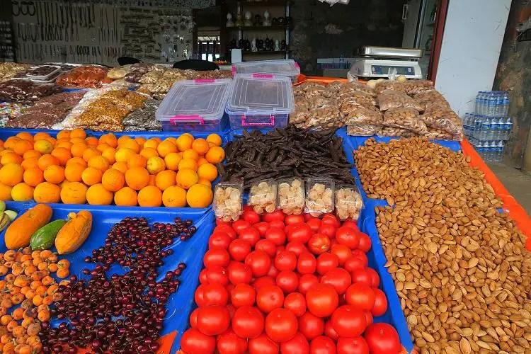Ein Stand mit Tomaten, Johannisbrot, Orangen, Kirchen und Nüssen.