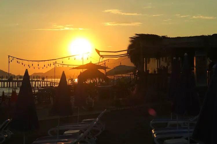 Die orange-rote Sonne geht hinter einer Strandbar in Alanya unter.