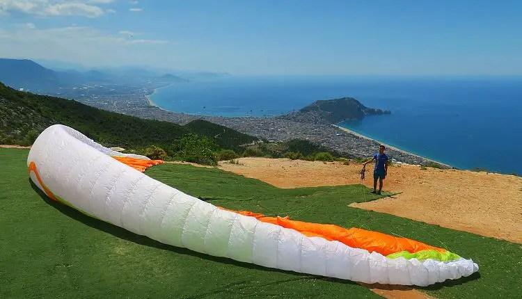 Ein Mann hält einen Paragliding-Schirm in seiner Hand der auf dem Boden liegt. Der Blick geht von der Spitze eines Berges bis weit hinaus auf das Meer und die Innenstadt von Alanya.