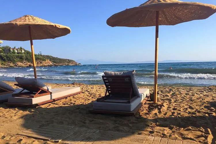 Die Sonnenliegen und Sonnenschirme am Sandstrand des Club Marvy Özdere am Tag bei schönem Wetter.