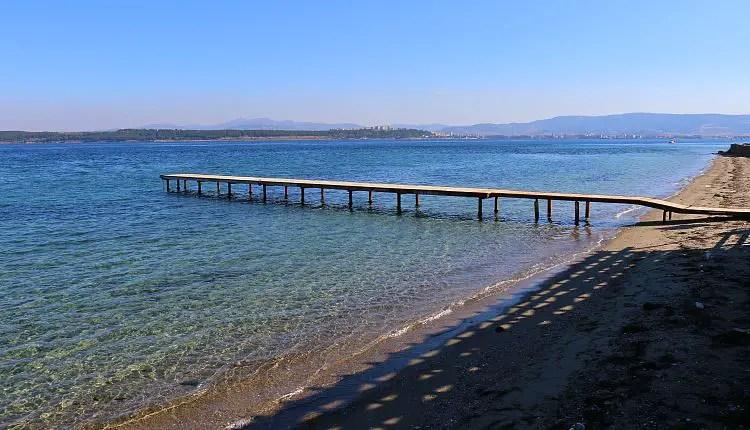 Sandstrand mit einem Steg und türkisblauen Wasser im Meer.