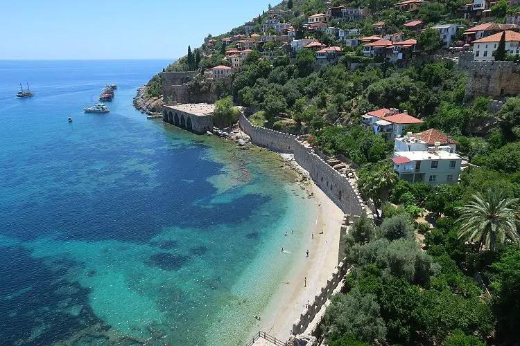 Türkisblaues Meer, die Hafenmauern, der Burgberg und das sonnige Wetter im Juni in Alanya.