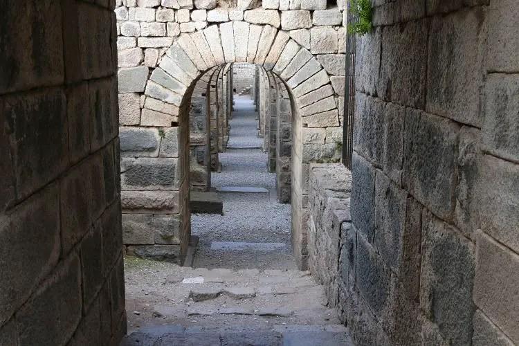 Rundbögen und Gang, aus großen Steinen gemauert.