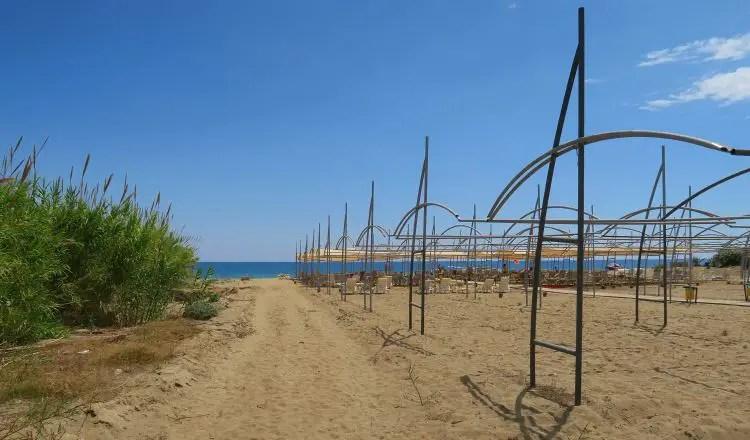 Sandstrand, Meer, ein Weg und Liegestühle im Hintergrund