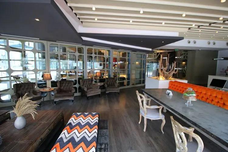 Business Lounge mit Tischen, Couch und Sesseln.