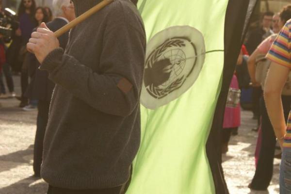 Um Anonymous e a bandeira dos Anonymous