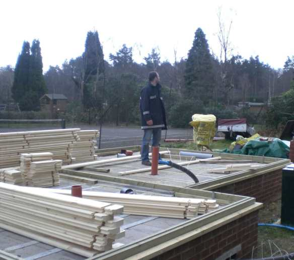A log cabin is built around a perimeter foundation beam, the floor joist and floor will go in after the cabin has been built.