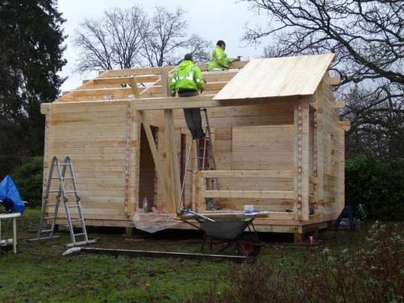 Roof being fitted and the whole build nearly complete of the log cabin