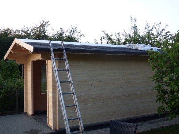 Roof shingles are fitted on top of the insulation board