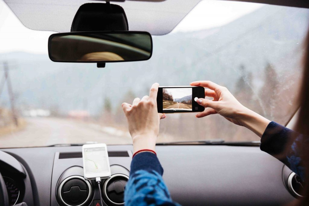 woman-hands-driving-and-taking-photos-with-mobil
