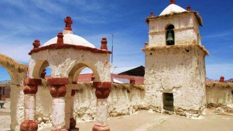 Iglesias-chile-region-Arica-Parinacota Se ve una iglesia de adobe pintada con cal blanca y un campanario