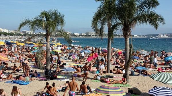 Una playa con muchos vacacionistas.