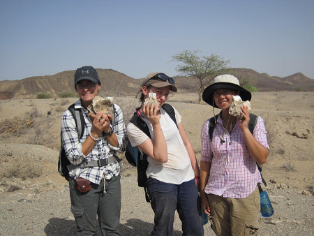Jayde, Anna, and Sam pose with both sides of a rhino mandible.