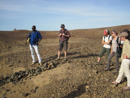 John Ekusi shows the field school the Middle Miocene excavation site that is being studied by Dr. Isaiah Nengo.