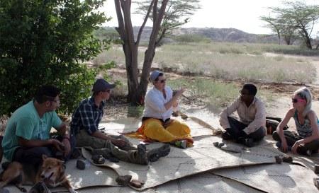 TBI students gather around as TA Hilary Duke provides some basic stone tool-making instructions.