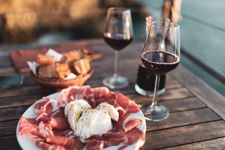 Calici di vino rosso toscano e prosciutto