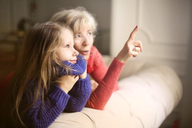 Nonna e nipote insieme che guardano fuori dalla finestra
