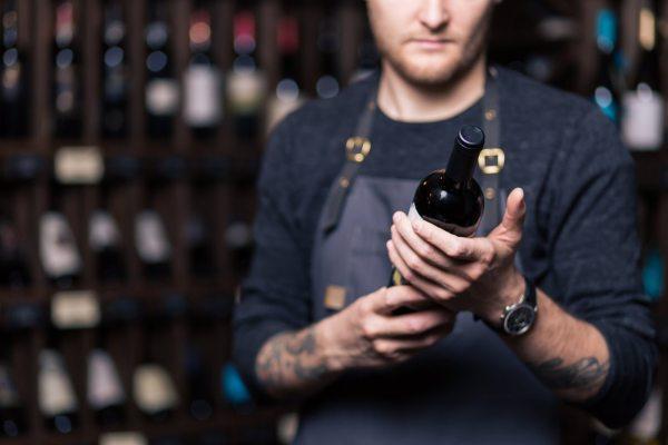 Sommelier sceglie una bottiglia di vino rosso
