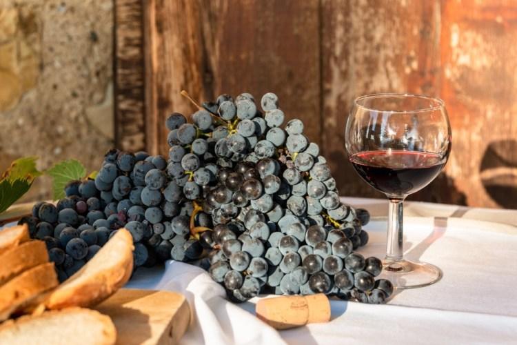 Bicchiere di vino rosso toscano accanto a grappolo d'uva