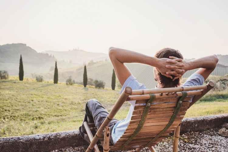 Ragazzo seduto guarda il panorama in Toscana
