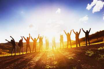 Gruppo di amici a braccia alzate al tramonto