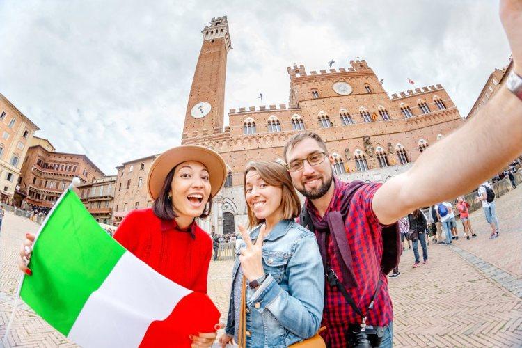 Tre ragazzi in viaggio a Siena in Piazza del Campo con bandiera italiana