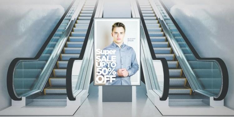 Cartellone pubblicitario tra due scale mobili nella metropolitana