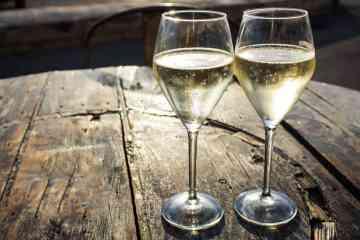 Due bicchieri di spumante toscano su una botte di legno