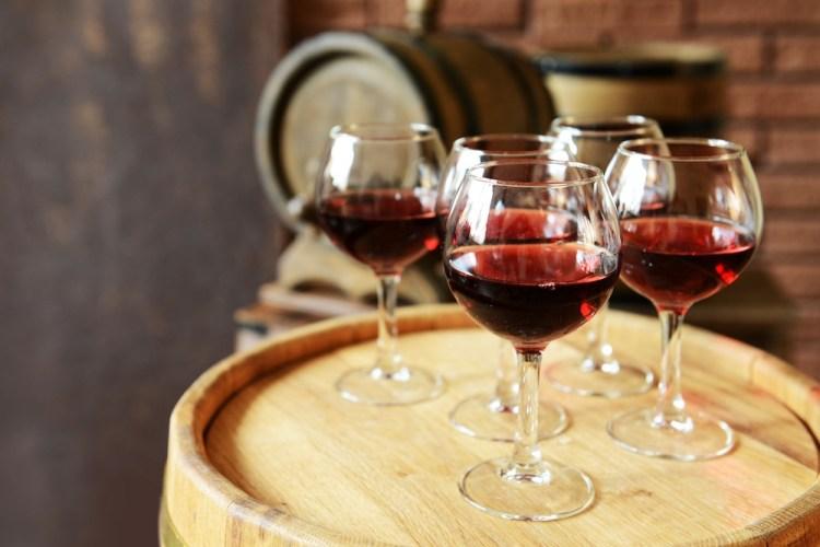 Bicchieri di vino rosso su una botte di legno