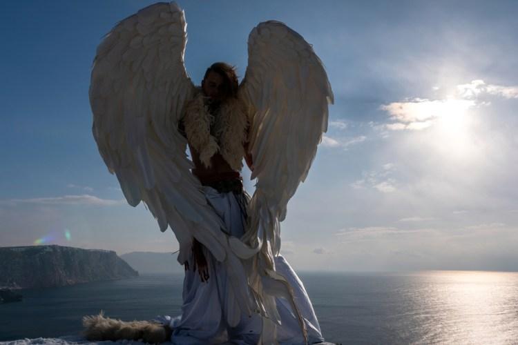 Un angelo custode di spalle su una roccia davanti al mare