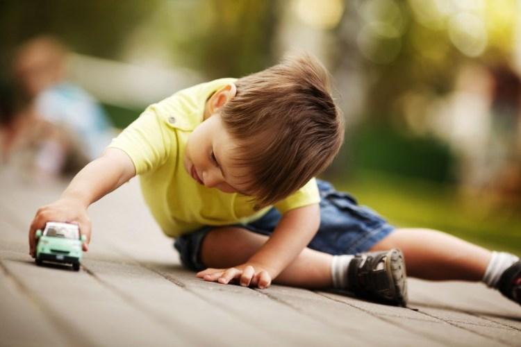Bambino con maglietta gialla gioca con macchinina verde