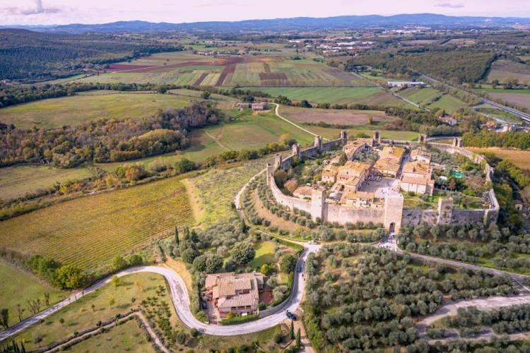 Il borgo toscano di Monteriggioni e i tornanti della strada vicina ripresi dall'alto
