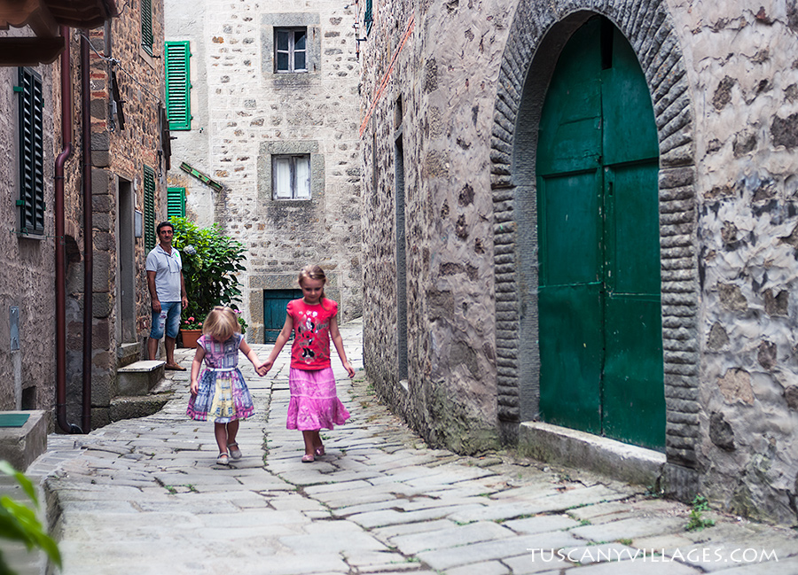 2 little girls walking in village street