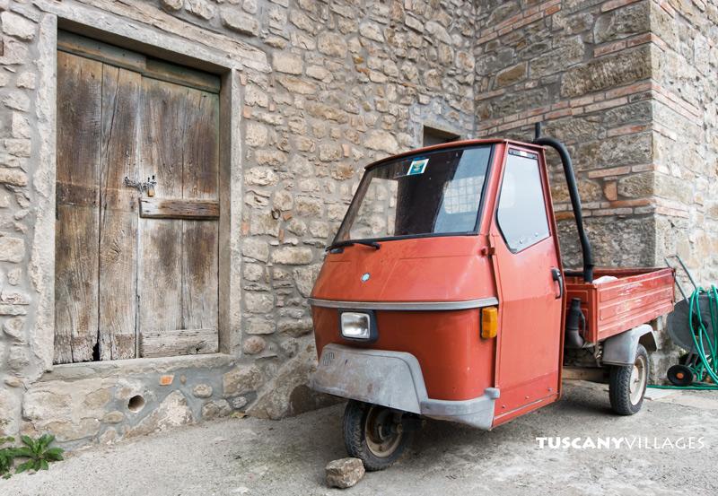 Orange ape and old door, Tuscany, Italy