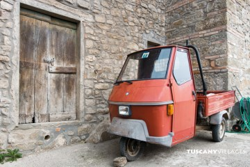 Orange ape and old door, Tuscany, Italy