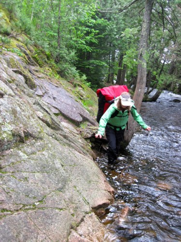 Kati tackles the Horsetail Rapids portage in high water on the Granite River