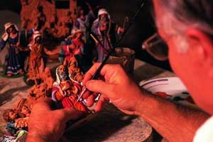 Artesano maltés pintando una figura del Belén