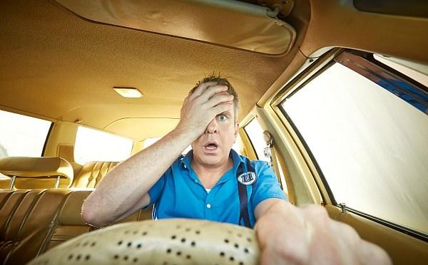A man behind the wheel of a car.