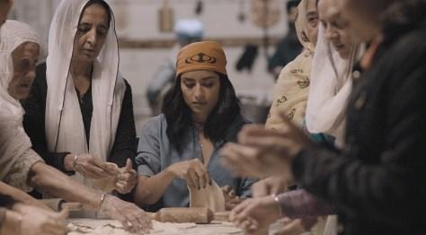 A woman kneads bread dough.
